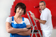 Couple painting wall in red