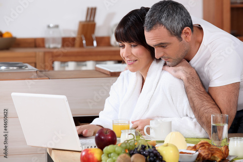 Couple eating breakfast together whilst browsing the internet