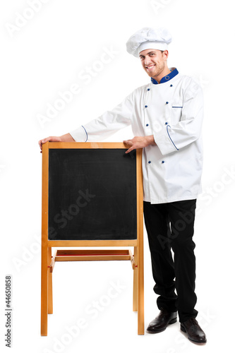 Smiling chef showing an empty blackboard
