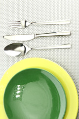 Green empty plates with fork, spoon and knife