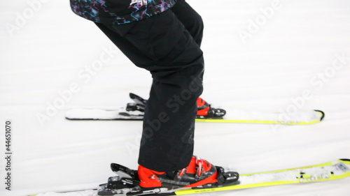 close-up of skiers legs with skis that ride on snow