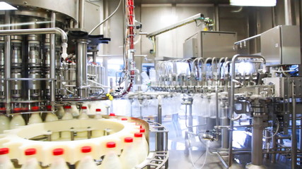 bottles filled with detergent rotated at huge milk factory