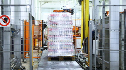 wrapper cuts off end stretch film, and bottles on pallet
