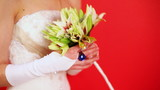 bride in white dress holding bouquet of lilies