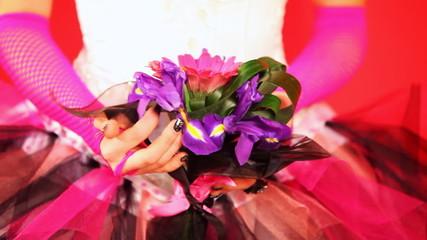 hands of bride in trendy wedding dress holding bouquet