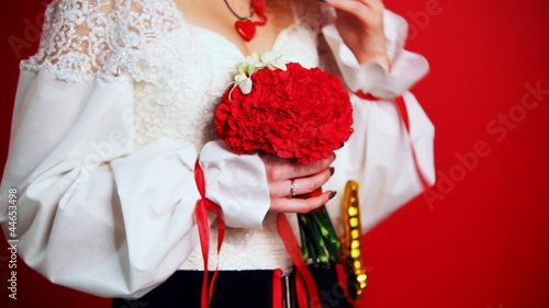 bride at wedding dress in folk style holding bouquet