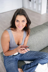Brunette reading text message whilst sitting on sofa