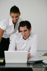 Two colleagues looking at laptop screen