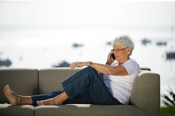 Senior woman making a telephone whilst sitting on outdoor sofa