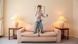 boy jumps on sofa at room with lamps on each side