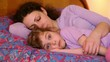 Mother and daughter lay on bed, mom sleeps but girl does not