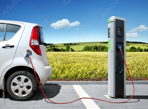 Leinwanddruck Bild E-Car an Ladestation vor Landschaft