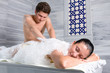 .  Male bath attendant massages and bathes young female customer