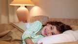 girl wakes and smile in bed at background of lamp