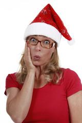 Blonde Frau mit Weihnachtsmütze und Hand am Gesicht