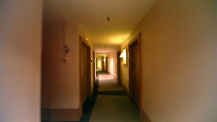 Lanterns on wall near door in dark corridor at hotel