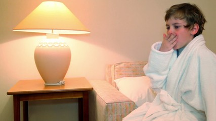 boy in bathrobe sit and yawns before lay to sleep on bed