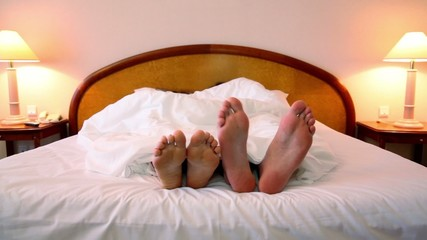 Man with woman lay in bed and moves shoeless feet