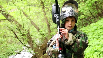 Boy with helm holds paintball gun