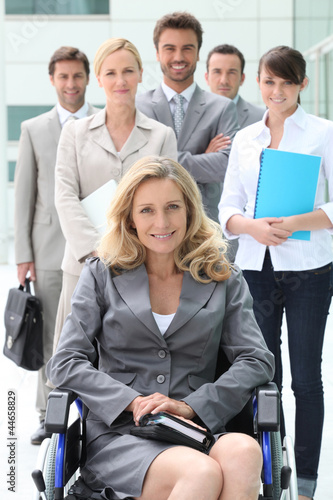 Businesswoman in a wheelchair with her colleagues