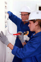 Electrician training his female apprentice