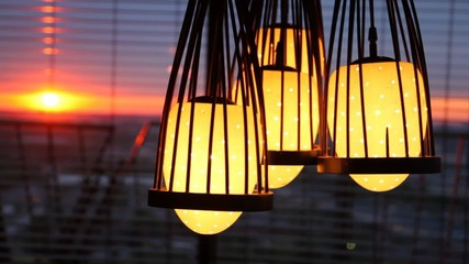 Four lamps hang before jalousie where sunset is visible