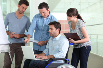 Businessman in wheelchair talking to colleagues