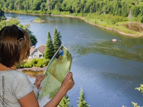 A tourist holding a map on a trail in Jacques - Cartier Park