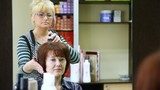 Hairdresser does hairdo by hair dryer for woman