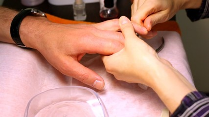 manicure cosmetician rubs butter for nails in of man
