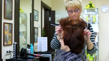 Woman-hairdresser at talk does a hairdress by thin hairbrush