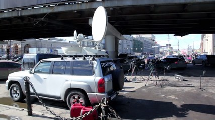 Car with satellite dish on roof and other tv equipment