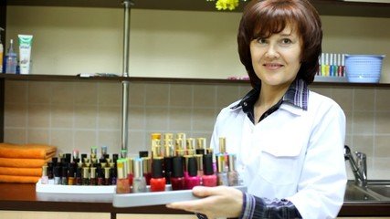 Woman-cosmetician represents nail polishes