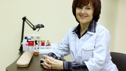 Woman-cosmetician sits at working table and includes lamp