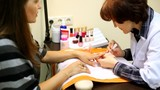 Woman does manicure in beauty salon