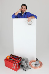 Plumber making a call whilst standing by a blank panel