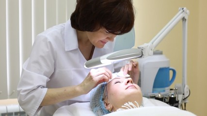 Cosmetician does disinfection of face  to client