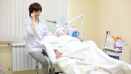 Patient lies in armchair and cosmetician speaks by phone
