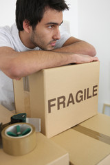 Man leaning on a stack of boxes