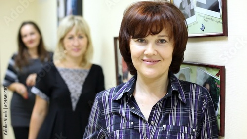 woman working in beauty salon affably looks and smiles
