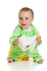 Child on potty play with toilet paper