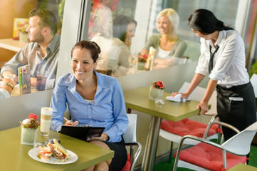 Businesswoman working in lunch break in cafe