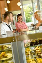 Waiter showing women cakes on window display