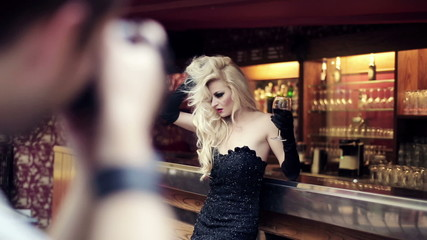 Beautiful woman on photo session in bar, steadicam shot