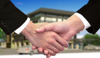Businessman hand shake hands in front of new home