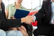 Handschlag im Autohaus vor Auto