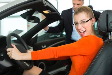 Junge Frau im Auto - Cabrio - in Autohaus