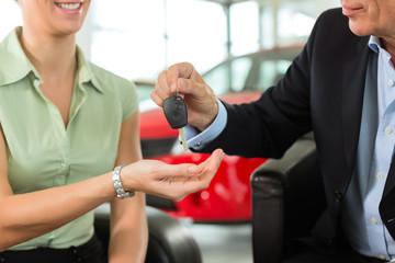 Mann übergibt Frau Autoschlüssel