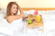 young beautiful woman in bed with light breakfast on wooden