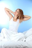 young beautiful woman in bed on blue background